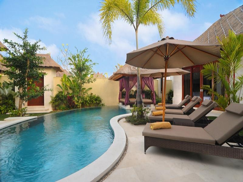 Villa stay during vacation with beautiful blue sky overlooking and tall trees and swimming pool.