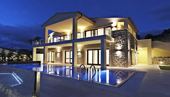 A beautiful villa with swimming pool brightly with lights brightly lip up.