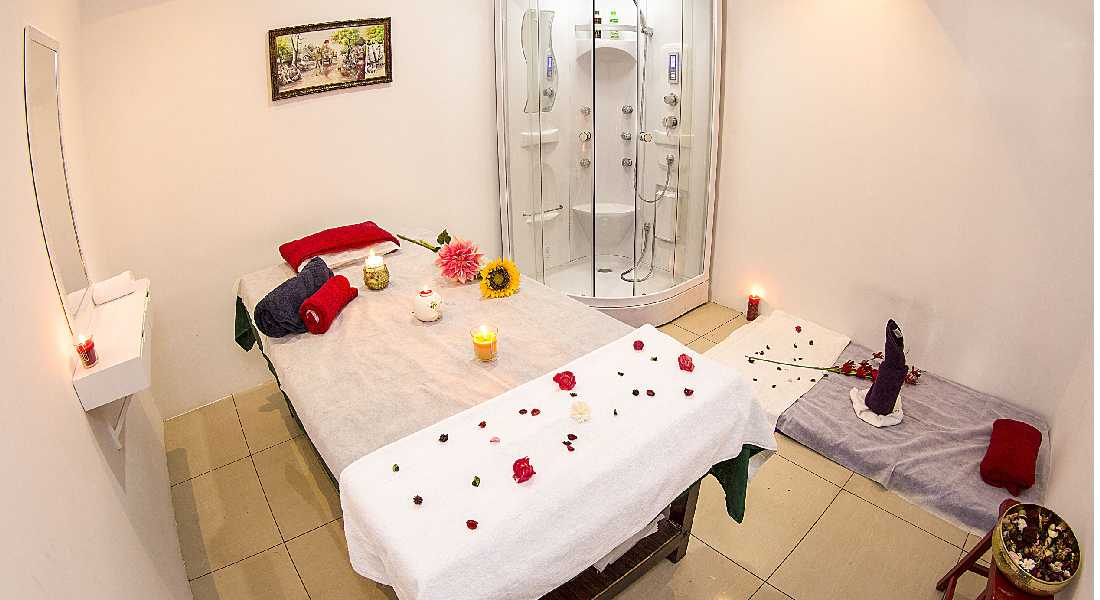 Spa and massage centre arranged with white towels, candles and flowers.