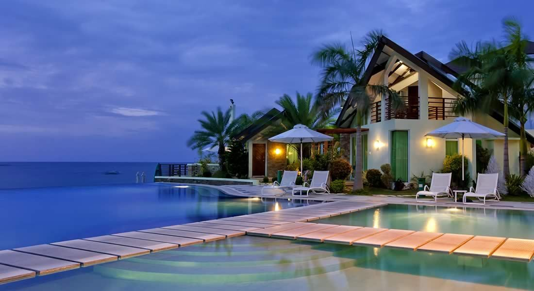 Sea side vacation villa surrounded by water and trees with beautiful view.
