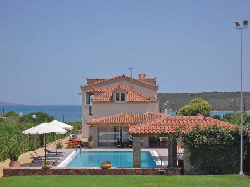 Villa for vacation surrounded with swimming pool and other amenities and an overlooking sky.